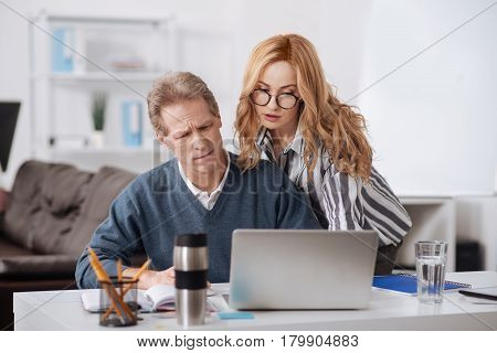 Inconvenient atmosphere. Charming young involved businesswoman standing in the office while using gadget and seducing colleague