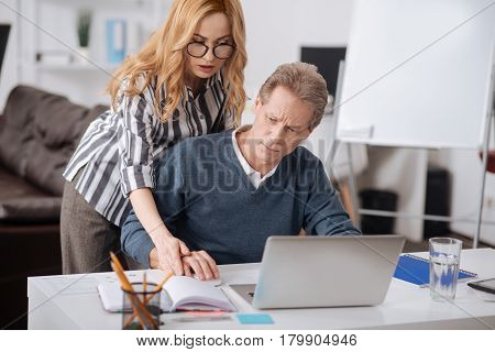 Unpleasant atmosphere around us. Strict rude involved businesswoman standing in the office while working and touching colleagues hand