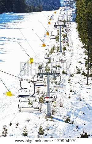 Chair ski lift elevator lifting people on the mountain ski slope Bansko Bulgaria ski centre