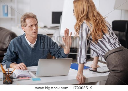 Stop doing this. Involved shocked mature manager sitting in the office and demonstrating negative emotions while working and expressing indignation towards colleagues seduction