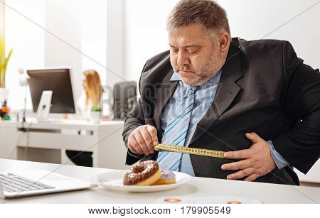 Lets have a look. Chubby unhealthy witty guy having concerns about his weight and trying seeing the scale of a problem while having a plate of doughnuts standing in front of him