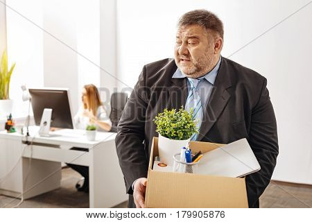 You gonna regret that. Confused mad chubby employee expressing his emotions while packing his things after being fired