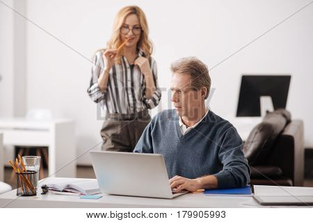 You are my goal. Resolute young positive woman standing in the office behind the colleague while expressing passionate emotions and seducing him