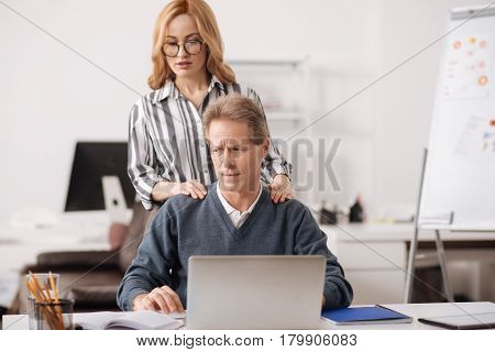 Let me relax you. Confident young careful businesswoman standing in the office behind the colleague while touching him and seducing