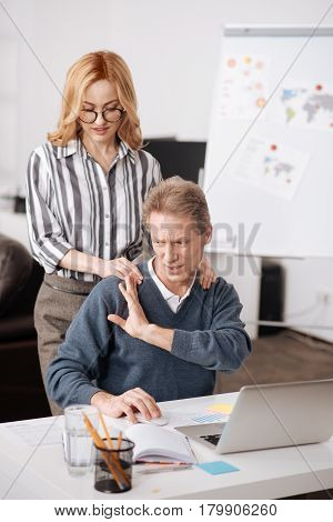 Not accepting this behavior. Perplexed puzzled elderly man sitting in the office and demonstrating irritation while working and expressing indignation towards coworker seduction