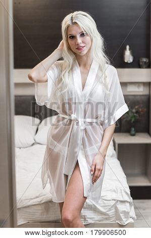 Young woman with white lingerie posing on bed