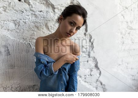 close up portrait of beautiful and slim brunette girl in blue denim shirt is at the white brick wall and looking at camera. shirt worn off the shoulder