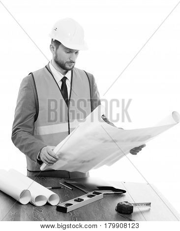 Improving project. Black and white studio shot of a mature businessman architect checking his building blueprints against white background profession occupation job career contractor builder concept