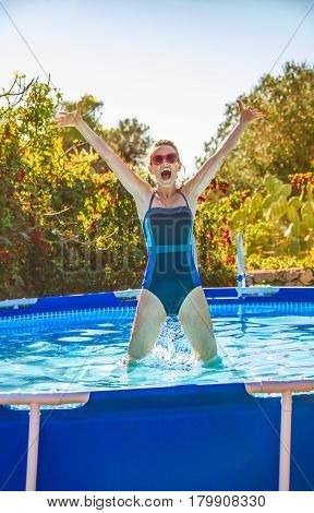 Happy Active Woman In Blue Swimsuit In Swimming Pool Jumping