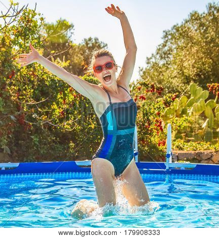 Happy Active Woman In Blue Swimwear In Swimming Pool Jumping