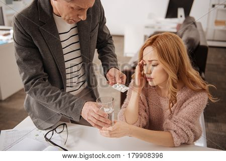 Expressing my help to you. Concerned helpful sincere businessman standing in the business center and expressing care while offering medicaments to the ill colleague