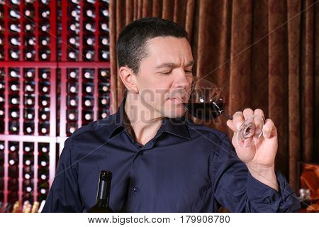 Handsome man tasting red wine