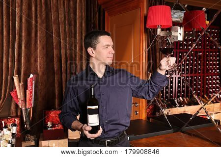 Man holding bottle and glass of red wine