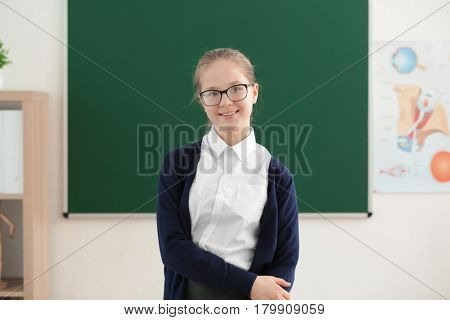 Cute girl standing near green school blackboard in classroom