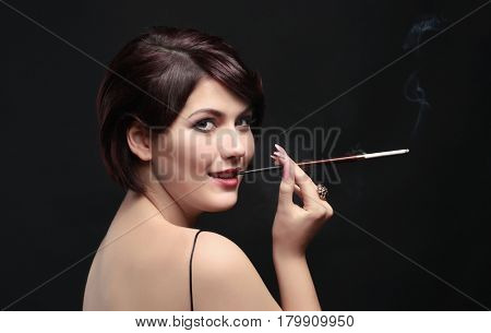 Young woman smoking with cigarette holder on dark background