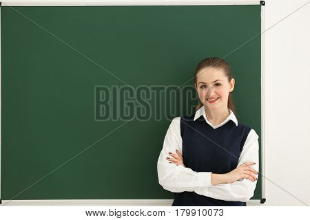 Smiling schoolgirl with crossed arms standing at blackboard in classroom