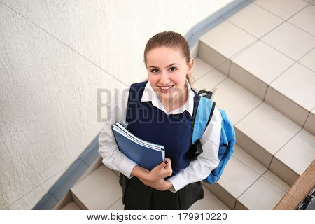 Cheerfully smiling school girl standing on stairs