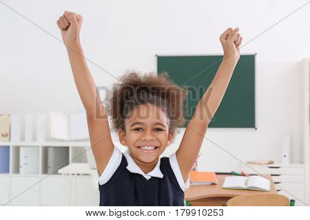 Portrait of cute African-American girl in classroom