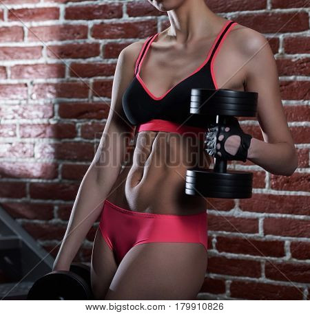 Living for sport. Cropped closeup of a female fitness trainer showing off her muscular abs while training using dumbbells