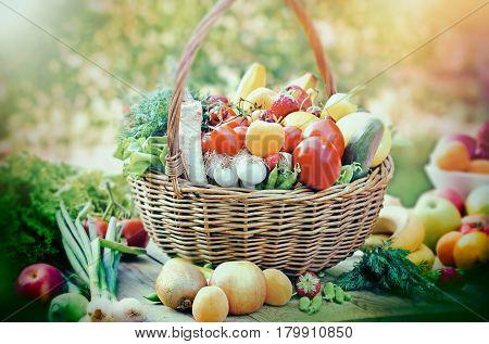Healthy food - vegetarian food in wicker basket and on table (fruit an vegetable)