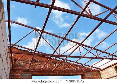 Industrial roofing. Metal roofing construction. Roofing Construction. New Steel roof trusses details with clouds sky background.