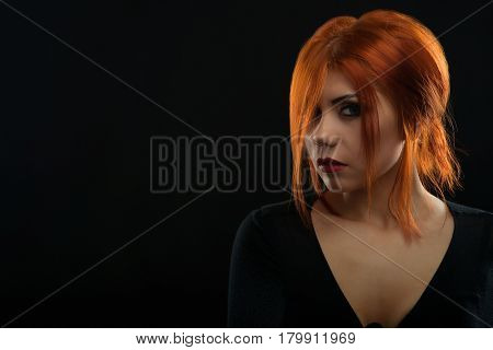 Mystical beauty. Closeup portrait of an attractive red haired young female looking mysteriously to the camera copyspace on the side