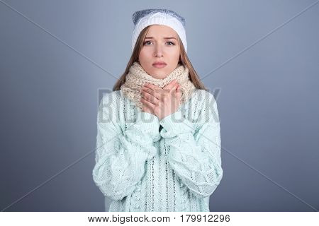 Sick young woman wearing warm scarf around neck on color background