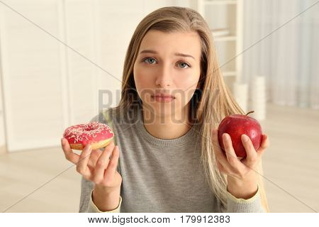 Beautiful young woman making choice between apple and doughnut