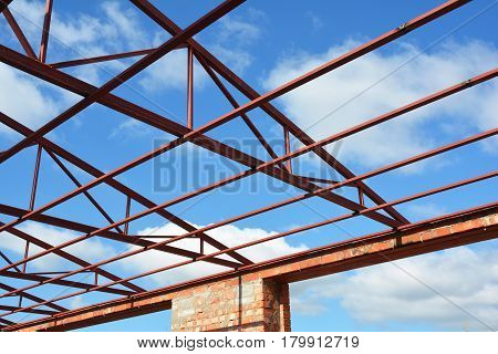 Metal roofing construction. Roofing Construction. New Steel roof trusses details with clouds sky background. Industrial roofing.