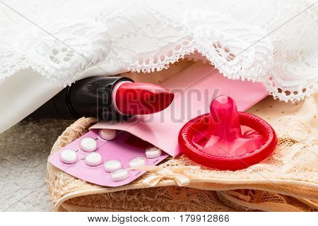 Healthcare medicine contraception and birth control. Closeup oral contraceptive pills condom and red lipstick on lace lingerie.