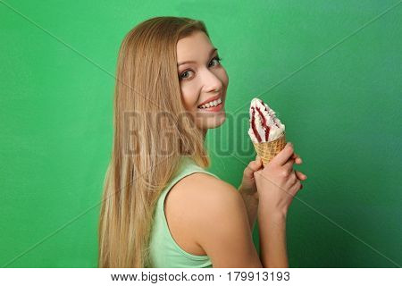 Beautiful young woman with ice cream on color background