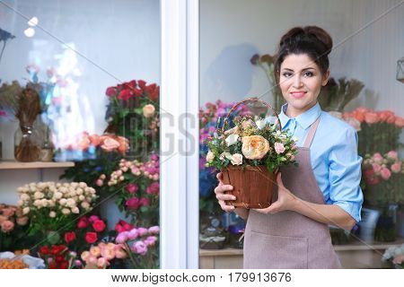 Beautiful woman florist holding basket with flowers in flower shop
