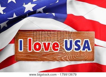 Wooden board with text I LOVE USA on American flag background