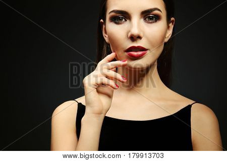 Portrait of beautiful young woman model with bright makeup on dark background