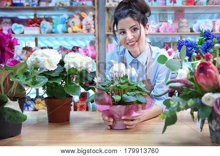Beautiful woman florist standing behind counter in flower shop