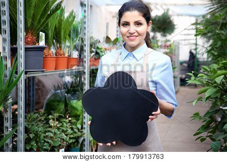 Beautiful woman florist holding board with space for text in greenhouse