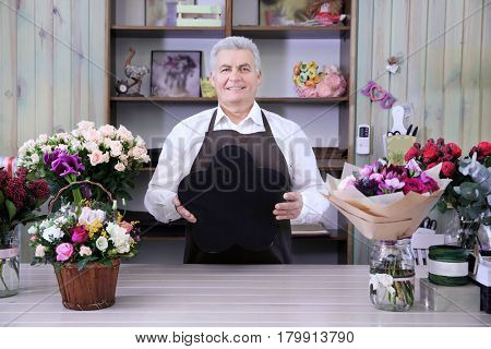 Male florist holding board with space for text in flower shop