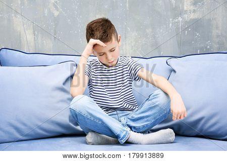 Cute boy suffering from headache at home