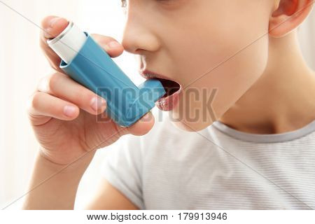 Boy using inhaler during asthmatic attack on light background, closeup