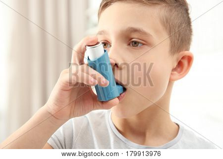 Boy using inhaler during asthmatic attack at home, closeup