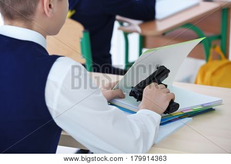 Closeup of schoolboy sitting at desk in classroom and holding gun
