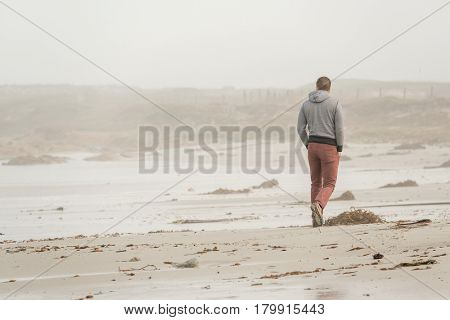 Lone man at beach, autumn. USA Pacific coast landscape, California