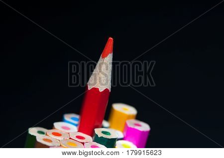 Red sharpened pencil among colorful crayons. Pencils background with copyspace. Shallow depth of field. Drawing and sketching supplies.