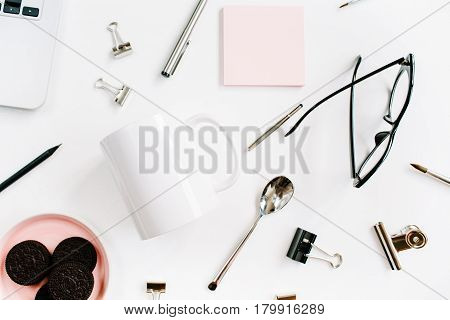 Home office desk with clean white mug cookies laptop spoon glasses and accessories. Flat lay top view. Business background.