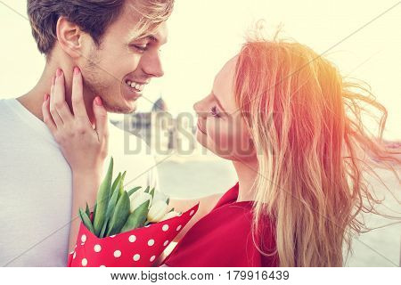 Youg couple with bouquet dating in sunset outdoor