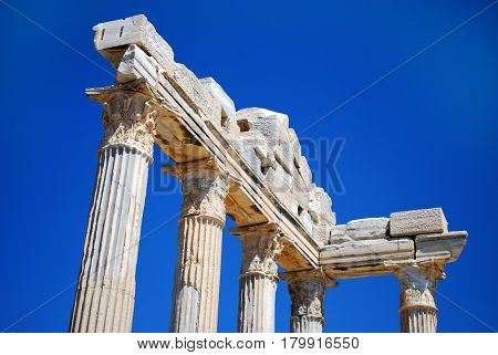 Ruined Columns of Ancient Greek Temple on Blue Sky Background