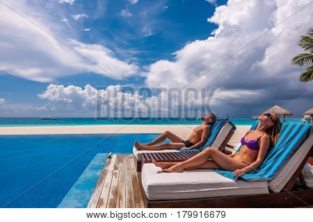 Couple relaxing in lounger at the poolside