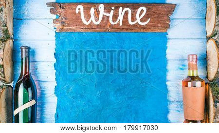 Wine bottles on blue painted wood with old paper frame and raw wood slices. Rustic signboard 'Wine' as title. Top view