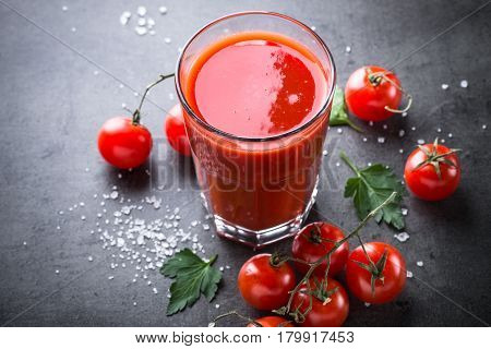Tomato juice and ingredients at dark slate table.