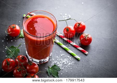 Fresh tomato juice and ingredients at dark slate table. Copy space